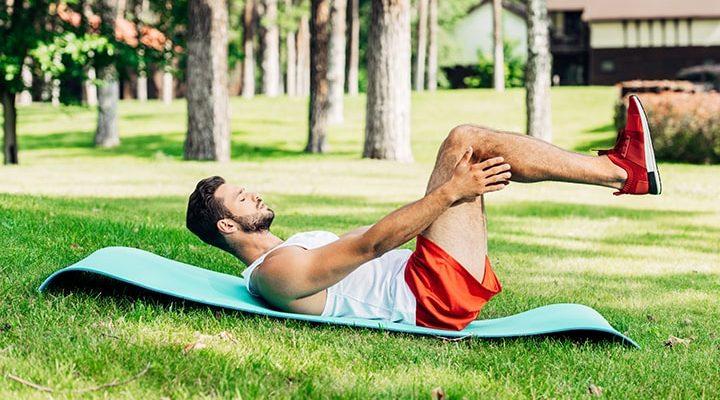 En man som ligger i gräset och tränar.