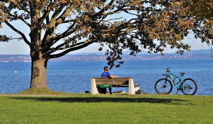 En cyklist som vilar på en bänk vid vattnet.
