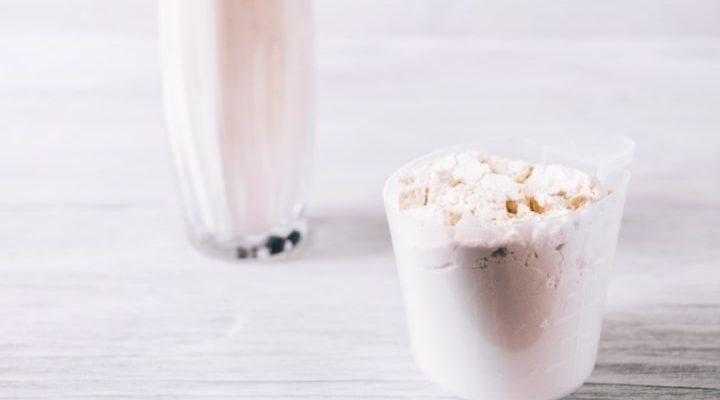 Ett mått med kaseinprotein och ett glas mjölk bakom.