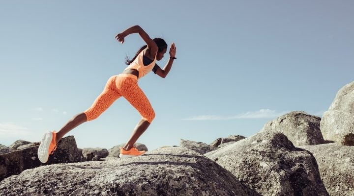 En kvinna med kompressions-tights som tränar uppe på ett berg.