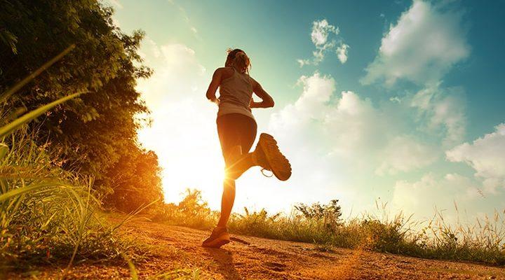 En person som springer på en stig i solnedgången.