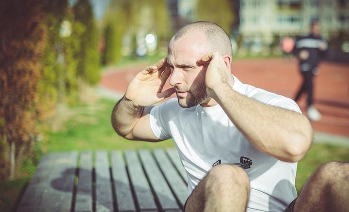 En man som tränar magen ut i solen.