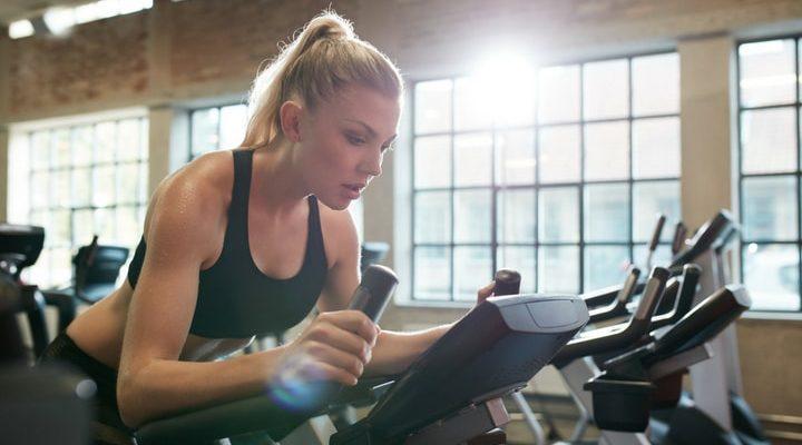 En tjej som cyklar på en motionscykel på gymmet.