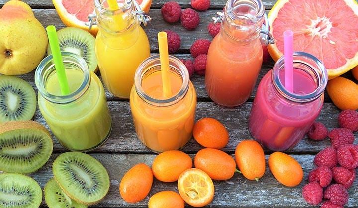 Flera olika smoothies och frukter på ett bord.
