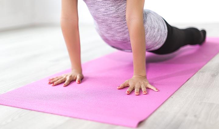 Kvinna ligger på en rosa yogamatta.