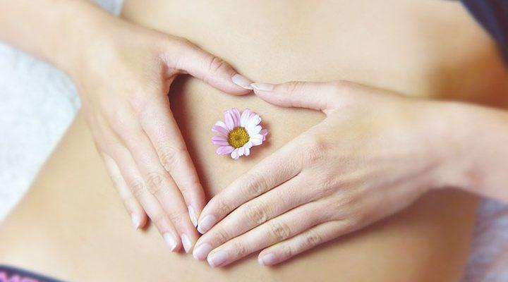 En kvinna som håller händerna som ett hjärta på magen.