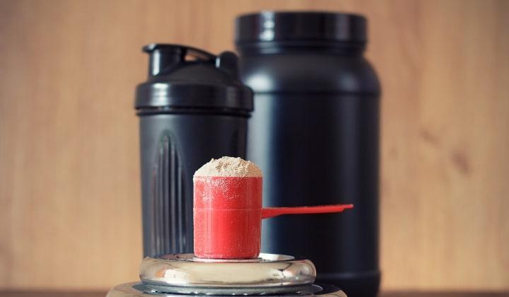 En skopa whey-proteinpulver framför en shaker och en burk.