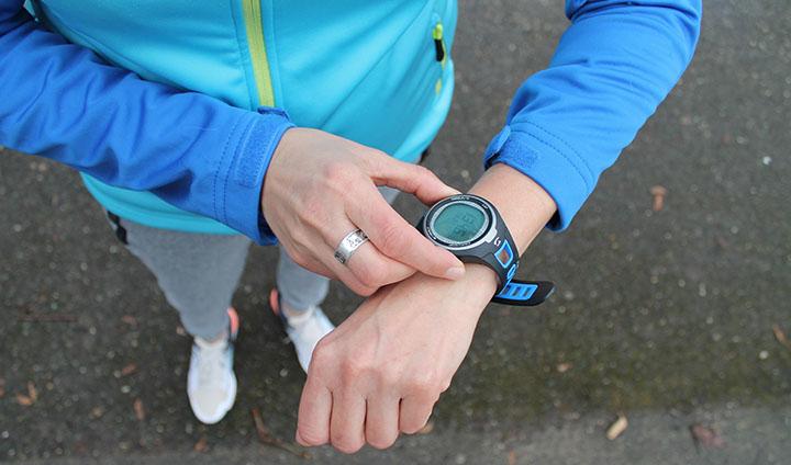 Person med träningskläder som tittar på sin pulsklocka.