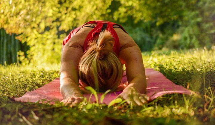 En person som gör yoga i gräset.