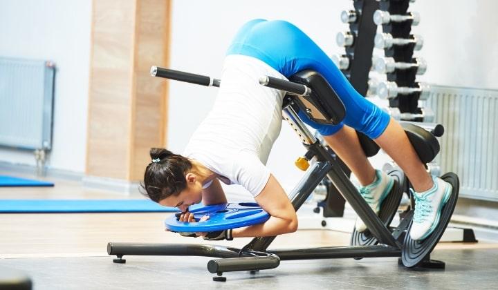 Kvinna som tränar på en ryggtränare.