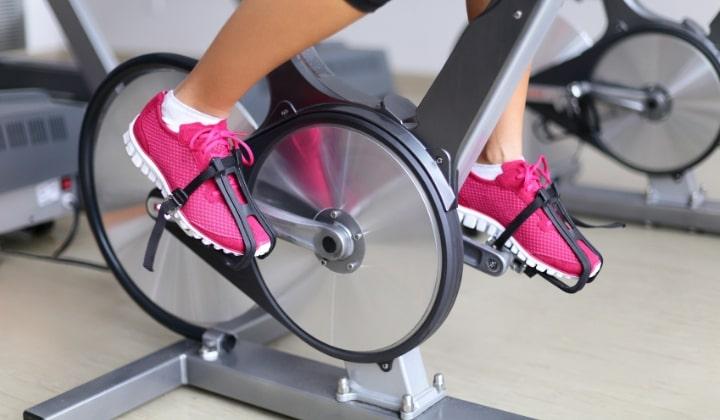 En person på en spinningcykel med rosa träningsskor.