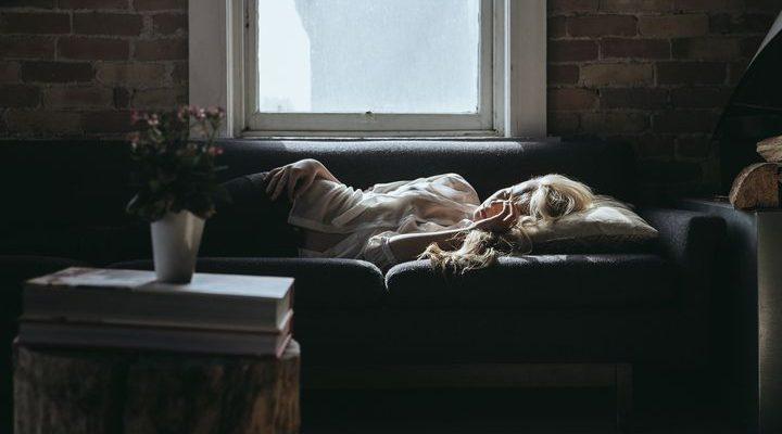 Kvinna ligger och sover på soffan.