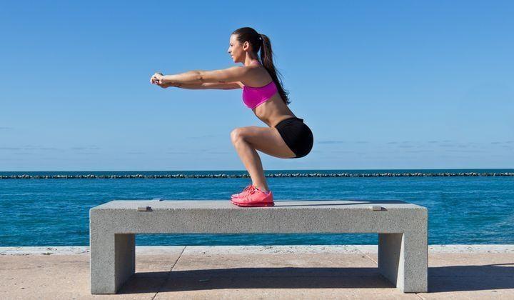 En kvinna som gör benböj på en bänk.
