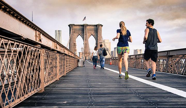 En man och en kvinna om är ute och springer på en bro.