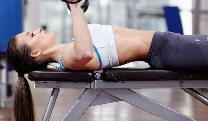 Kvinna som ligger på träningsbänk med hantlar.