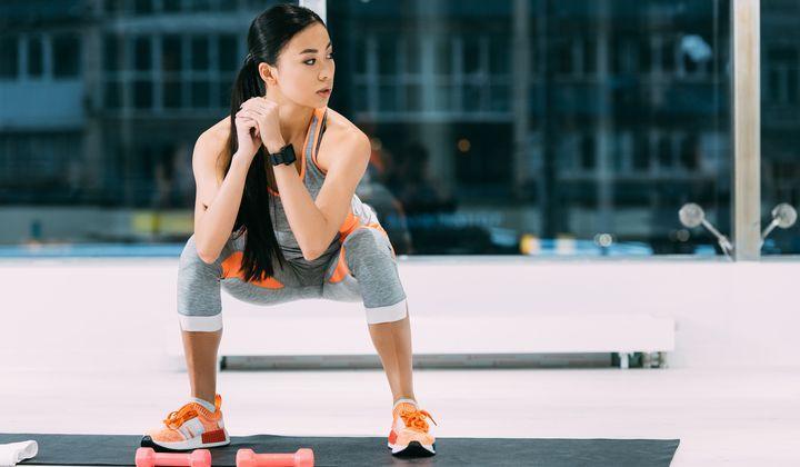 En tjej som gör en squat och tränar rumpan.