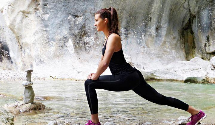 En tjej som står vid vattnet och tränar.