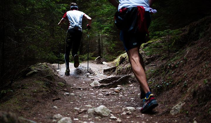 Två personer som är ute och springer i skogen.