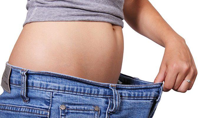 En person som står med ett för stora byxor och håller ut dom från magen.