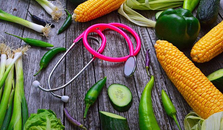 Nyttig mat och ett stetoskop på ett bord.