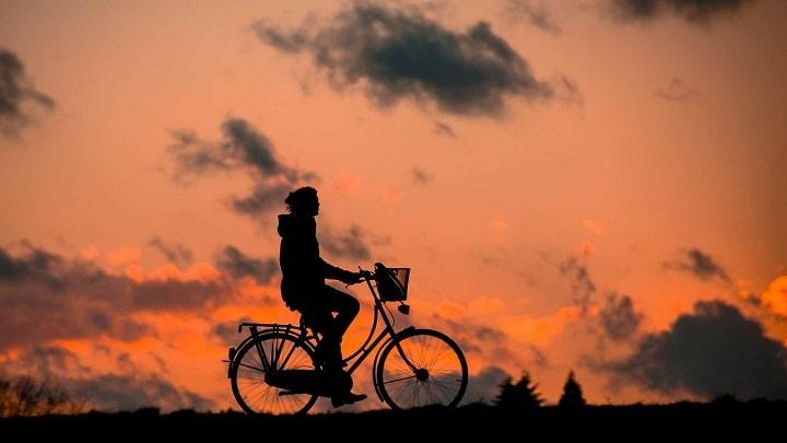 woman silhouette sunset biking