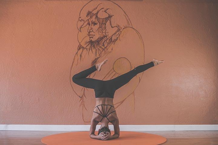 Kvinna står på huvudet på en yogamatta.