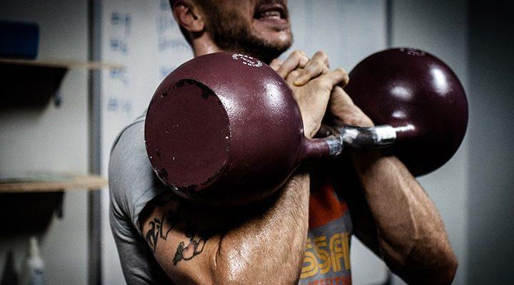 En man som tränar med ett par kettlebells.